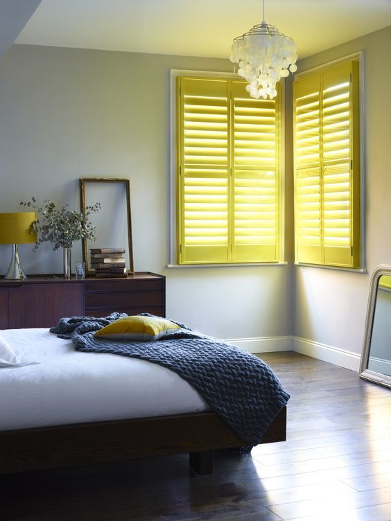 colourful yellow painted timber shutters to match bedroom decor on the Gold Coast